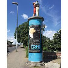 Die 1,90 m grosse Originalskulptur auf einer Litfass-Säule ist in Düsseldorf zu sehen.